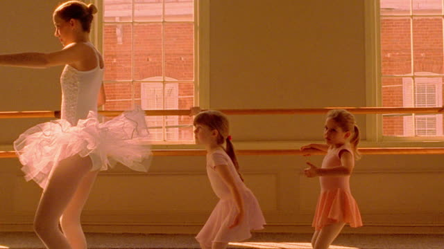 orange ms dolly shot ballerina teaching young girls at barre / window in background - barre stock videos & royalty-free footage
