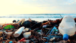 4K dolly shot: Beach polluted with plastic bottles