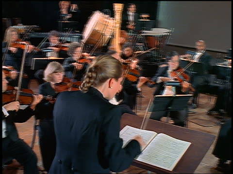 dolly shot behind female conductor of orchestra playing - musical conductor stock videos & royalty-free footage