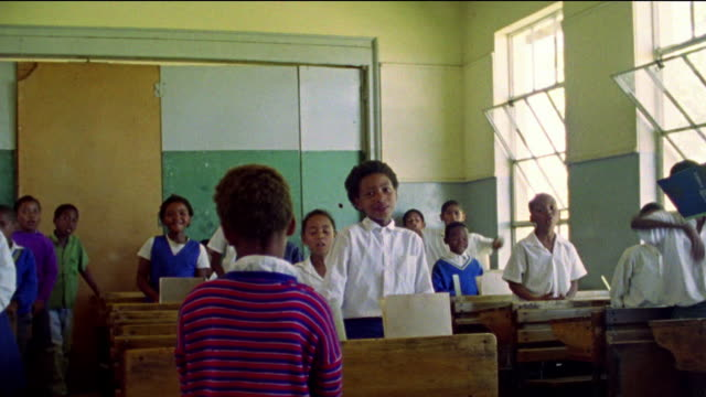 dolly shot black children stand next to desks in classroom and speak with back of child in foreground / south africa - schoolboy stock videos and b-roll footage