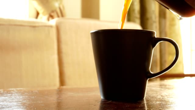 dolly shot: black coffee pouring into a cup, hand stirring, and picking a cup in living room - home indoor scene