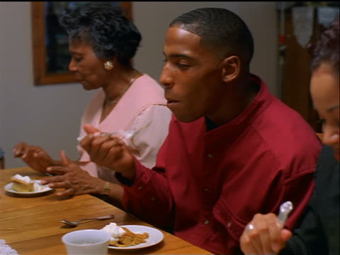 vídeos de stock, filmes e b-roll de dolly shot pan black family eating pumpkin pie at holiday table / thanksgiving - pie humano