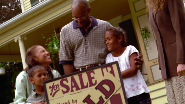 canted ms dolly shot black family hugging + standing with female real estate agent in front of house with 'sold' sign - real estate sign stock videos & royalty-free footage