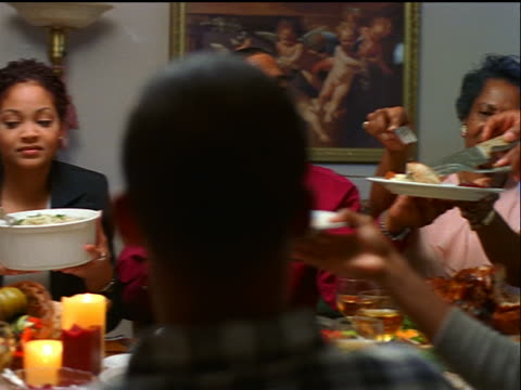dolly shot black family passing food around holiday table / senior man cutting + serving turkey - thanksgiving stock videos & royalty-free footage