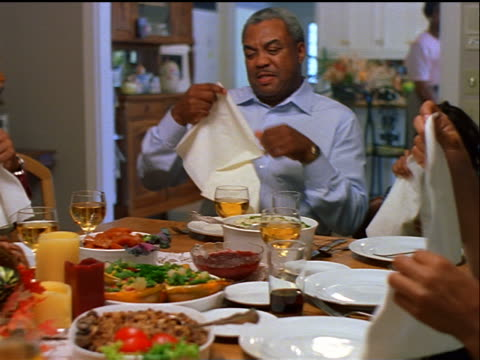dolly shot Black family sitting at holiday table placing napkins on laps / Thanksgiving