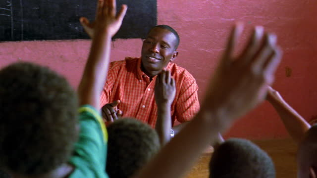 MS dolly shot Black schoolchildren raising hands with teacher pointing at them in classroom / Kenya