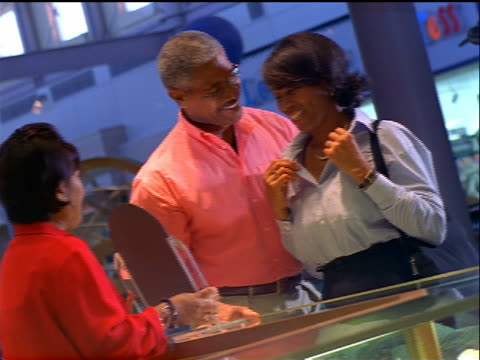 CANTED dolly shot Black woman looking at necklace in mirror in store as man + saleswoman watch
