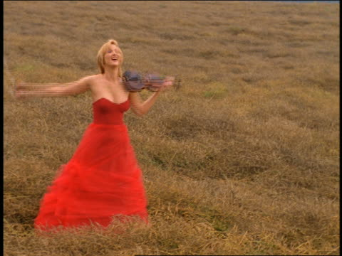 dolly shot blond woman in formal red dress with violin bowing in grassy field - menschlicher arm stock-videos und b-roll-filmmaterial
