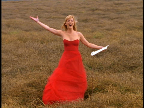 dolly shot blond woman with music stand in formal red dress with arms raised singing in grassy field - human limb stock videos & royalty-free footage
