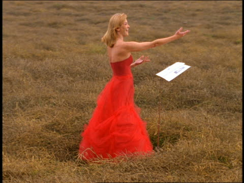 vidéos et rushes de dolly shot blond woman with music stand wearing formal red dress singing + bowing in grassy field - robe rouge
