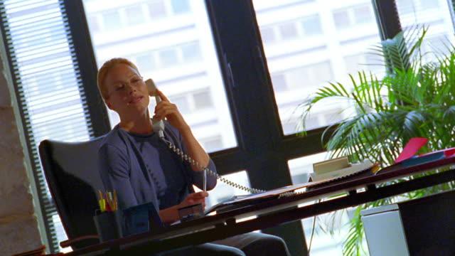 vídeos de stock e filmes b-roll de canted ms dolly shot blonde businesswoman talking on phone at desk in office - sentar se
