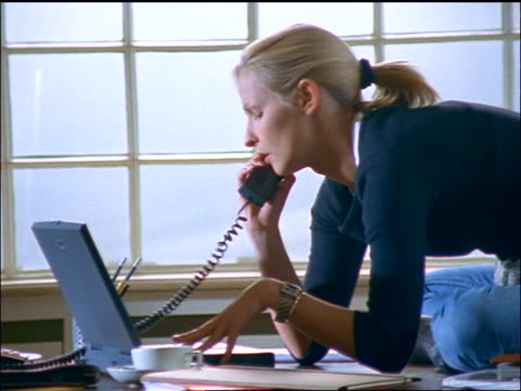 dolly shot blonde woman talking on telephone + working on laptop sitting on desk in home office - landline phone stock videos & royalty-free footage