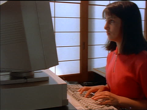 dolly shot brunette girl typing on computer / shoji screens in background - anno 1997 video stock e b–roll