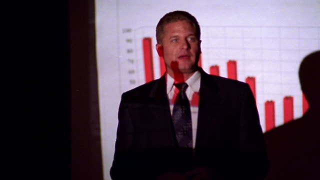 ms dolly shot businessman giving presentation with projected bar chart + laser pointer - training course stock videos & royalty-free footage