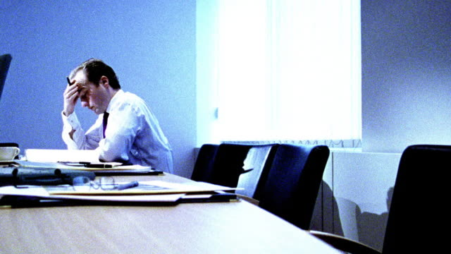 BLUE OVEREXPOSED dolly shot businessman looking stressed alone at table in conference room after meeting