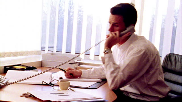 OVEREXPOSED dolly shot businessman talking on phone + looking through papers on desk in office /window in background