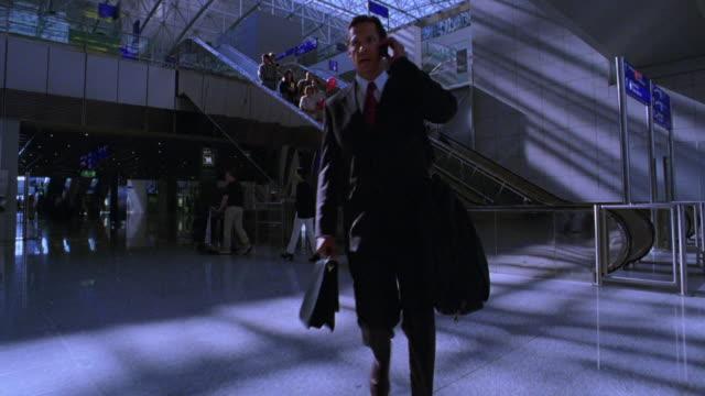 BLUE dolly shot businessman walking talking on cell phone in Frankfurt Airport Terminal / Frankfurt, Germany