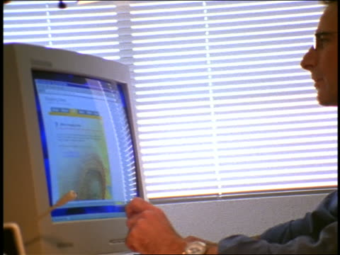 dolly shot businessman working on computer flipping through desk calander - 1999 stock videos & royalty-free footage