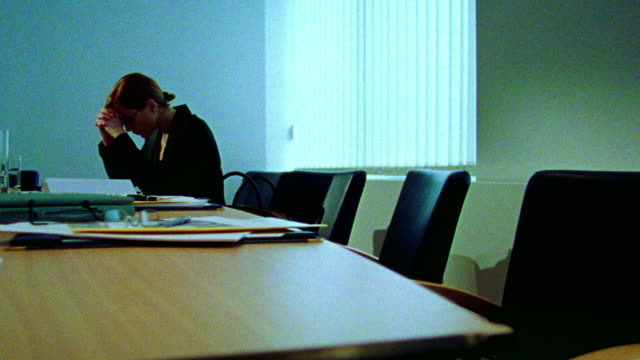 blue dolly shot businesswoman looking stressed sitting alone at table in conference room after meeting - 月経前緊張症候群点の映像素材/bロール