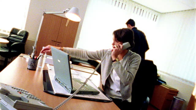 overexposed canted dolly shot businesswoman on telephone at desk in office / man in background looking at papers - overexposed video stock e b–roll