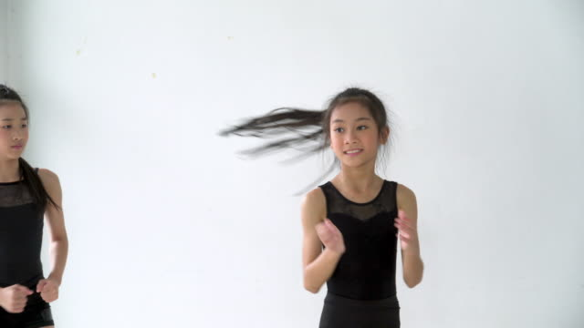 dolly shot by handheld : cute girl dancer and partner practice jazz dance together - flexibility stock videos & royalty-free footage