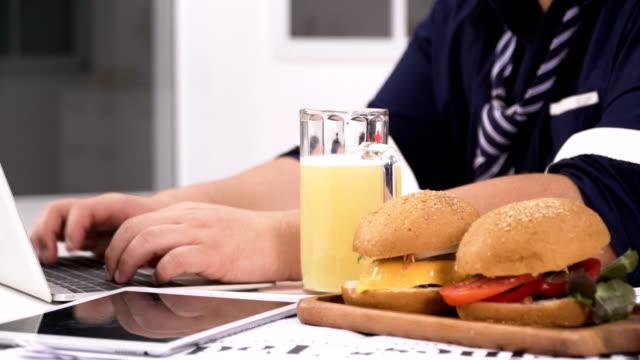 台車側面撮影: 太りすぎのハンバーガーやビールなどの不健康な食品のラップトップに入力するタイの実業家の手 - unhealthy eating点の映像素材/bロール
