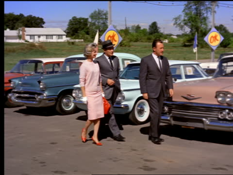 1962 dolly shot car salesman + couple walking on car lot looking at new cars - 1962年点の映像素材/bロール