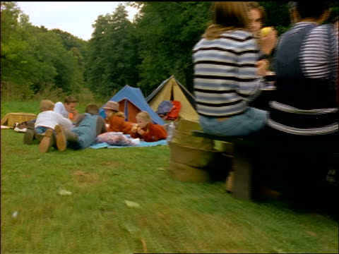 stockvideo's en b-roll-footage met dolly shot children eating on blankets near adults eating at picnic table at campsite / self-conscious girl - belgië