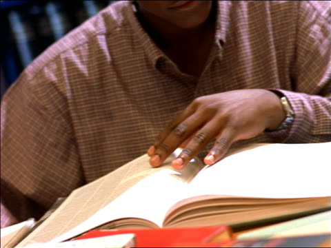 vidéos et rushes de dolly shot close up black male college student studying at table in library study area / boston, ma - étudiant