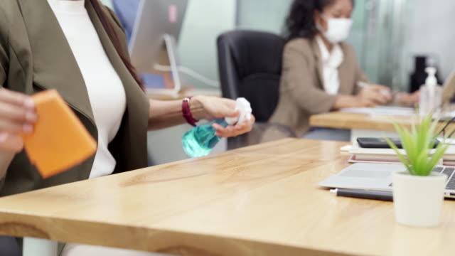 vídeos de stock, filmes e b-roll de 4k uhd dolly shot: feche a mesa de desinfecção e limpeza da empresária antes de começar a trabalhar com laptop em novo escritório normal de distância social. todos os funcionários usam máscara facial protetora para reduzir o risco de infecção pel - limpando atividade móvel