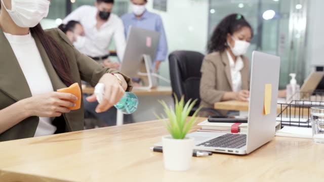 vidéos et rushes de 4k uhd dolly shot: fermez la désinfection femme d'affaires et la table de nettoyage avant de commencer à travailler avec ordinateur portable dans le nouveau bureau de distance sociale normale. tous les employés portent un masque protecteur pour rédui - agence de design