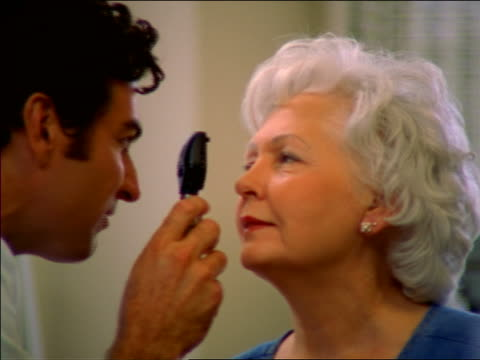 dolly shot close up doctor examining senior womans eyes