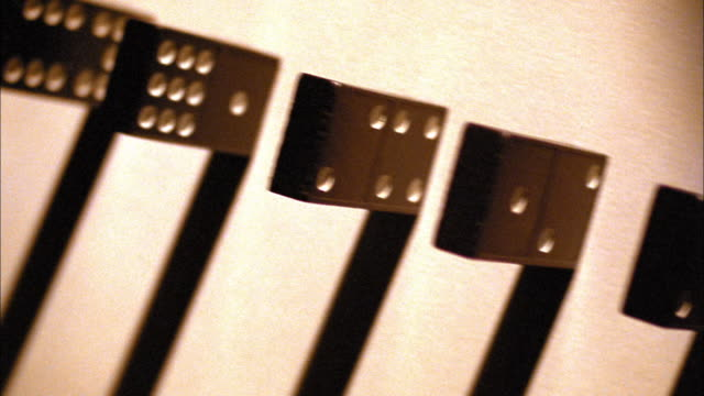 TINTED OVERHEAD dolly shot close up dominoes falling in line with shadows