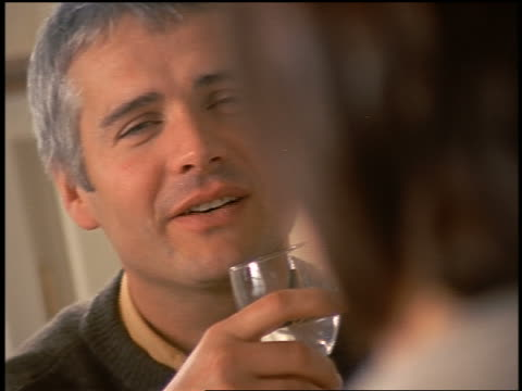 dolly shot close up man with graying hair holding glass with water talking at family dinner - one mid adult man only stock videos & royalty-free footage