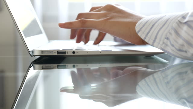 dolly shot: close up woman's hand typing on laptop - log on stock videos and b-roll footage