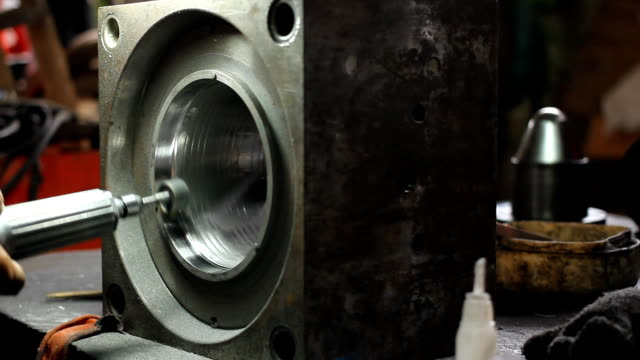 dolly shot: close up workers operate an industrial grinder on a piece of steel. - bugtiger stock videos and b-roll footage