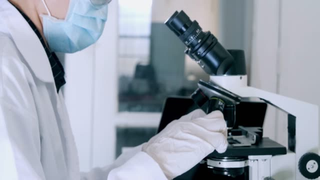 dolly shot :close-up,researcher working in lab with microscope.female biochemist analyzing bacteria sample on microscope, medicine - biochemist stock videos and b-roll footage