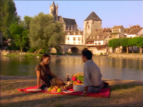 dolly shot couple having picnic on riverbank / French village in background / France