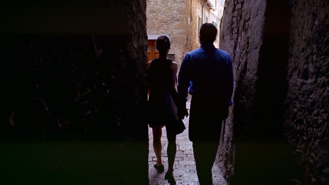 dolly shot couple holding hands walking away from camera in narrow outdoor hallway / Florence, Italy