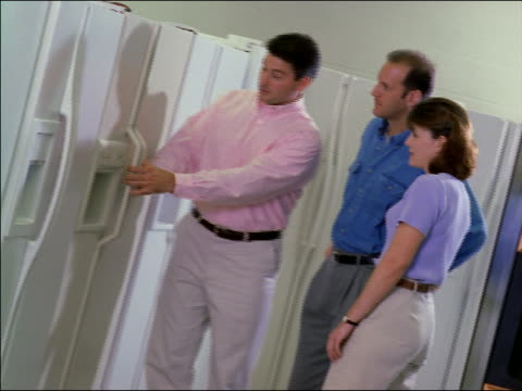 dolly shot couple looking at refrigerators in store with salesman demonstrating - femmina con gruppo di maschi video stock e b–roll