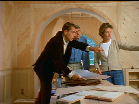 vídeos y material grabado en eventos de stock de dolly shot couple + male architect in unfinished house pointing to + discussing something offscreen - mujer con grupo de hombres