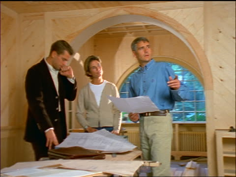 vídeos y material grabado en eventos de stock de dolly shot couple + male architect looking at plans then pointing to + discussing something offscreen - mujer con grupo de hombres