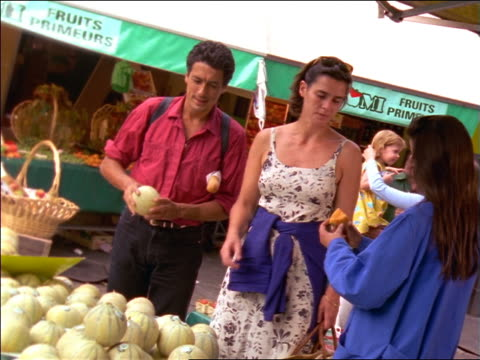 dolly shot couple sampling melon from vendor in outdoor market / france - paar mittleren alters stock-videos und b-roll-filmmaterial