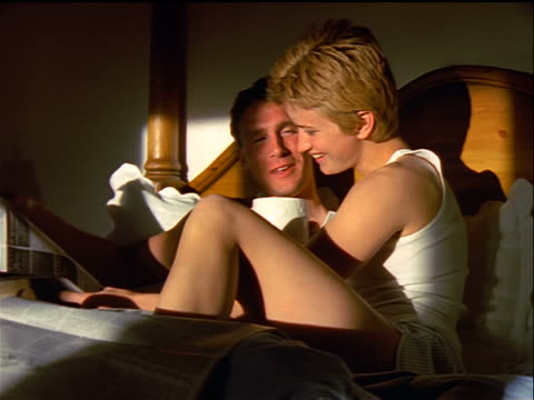 dolly shot couple sitting in bed reading newspaper + talking / woman holding coffee cup
