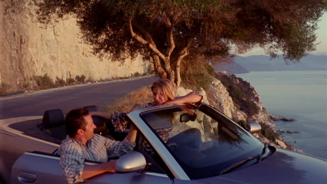 Dolly shot couple sitting in convertible exchanging caresses / smiling and looking at view / Corsica