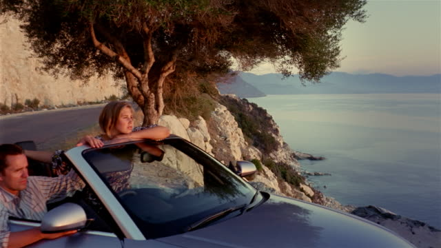 dolly shot couple sitting in convertible / man caressing woman's face /smiling and looking at view / corsica - 年の差カップル点の映像素材/bロール