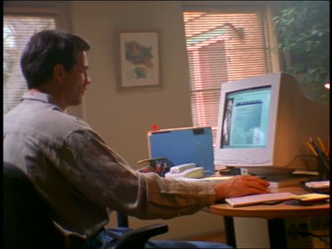dolly shot couple working on computer together in living room - archival stock videos & royalty-free footage