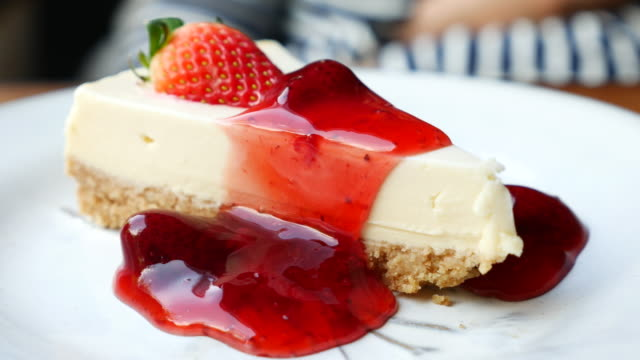 dolly shot: delicious homemade cheesecake with strawberries jam - tart dessert stock videos & royalty-free footage