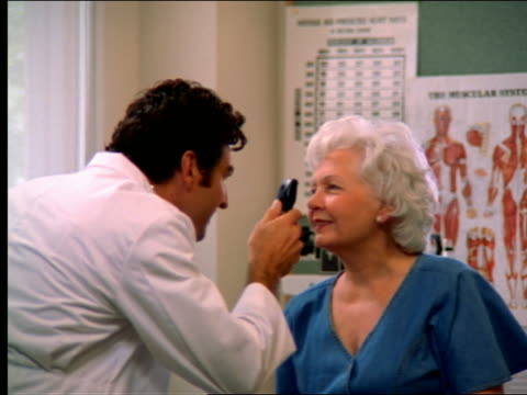 stockvideo's en b-roll-footage met dolly shot doctor examining senior woman's eyes - oogmeetkunde