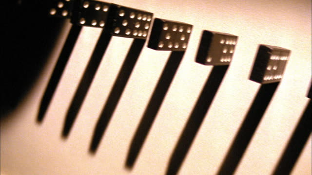 TINTED OVERHEAD dolly shot dominoes falling in line with shadows